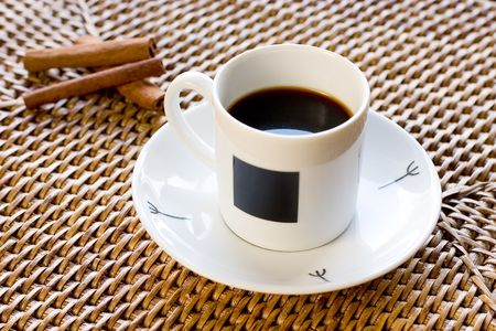 White cup of coffee in rattan with cinnamon Stock Photo