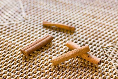 Pile of cinnamon sticks shot on rattan