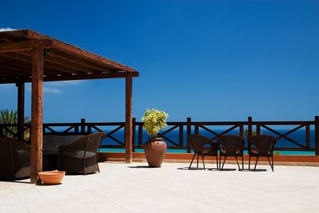 Balcony with 3 rattan chairs and ocean at the background