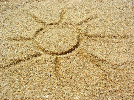drawing of the sun in the sand at the beach Stock Photo