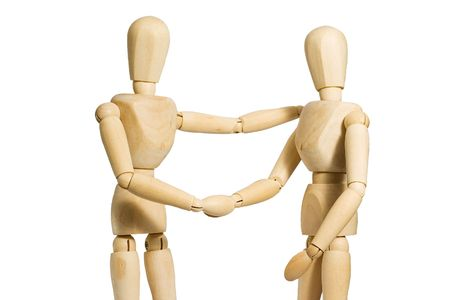 Two wood models shaking hands with clipping path