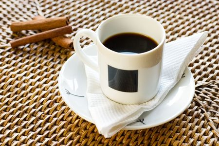 White cup of coffee in rattan with cinnamon photo