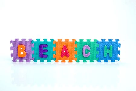 Colorful toy letters on spelling beach isolated in white background photo