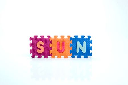 Colorful toy letters on spelling sun isolated in white background photo