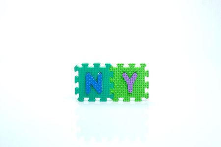 ny: Colorful toy letters on spelling ny isolated in white background