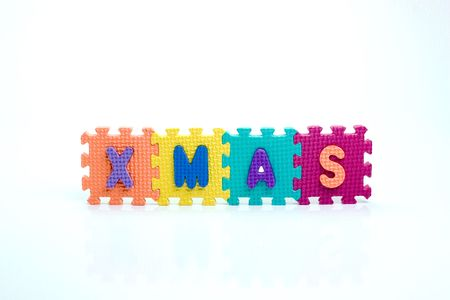 Colorful toy letters on spelling xmas isolated in white background photo
