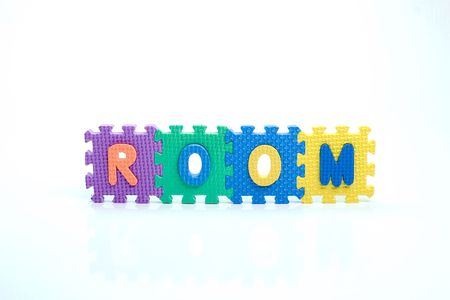 Colorful toy letters on spelling room isolated in white background