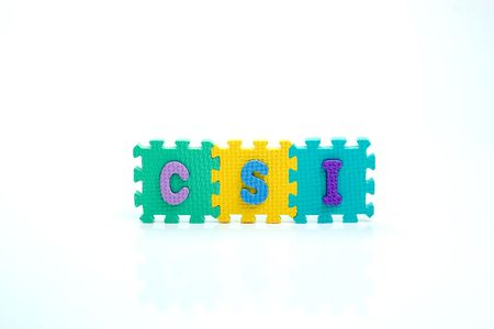 Colorful toy letters on spelling CSI isolated in white background photo