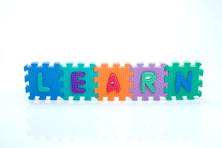 Colorful toy letters on spelling learn isolated in white background photo