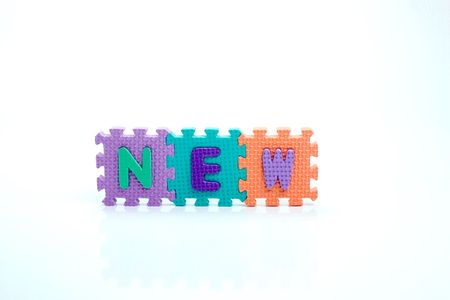 Colorful toy letters on spelling new isolated in white background photo