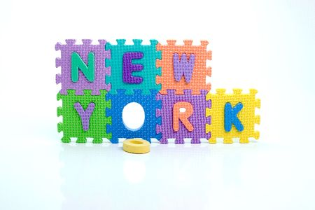 Colorful toy letters on spelling New York isolated in white background photo