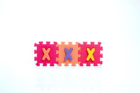 Colorful toy letters on spelling XXX isolated in white background Stock Photo - 1015605