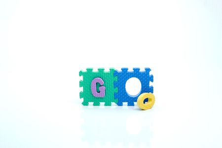 Colorful toy letters on spelling go isolated in white background