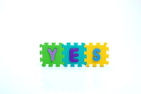 Colorful toy letters on spelling YES isolated in white background Stock Photo