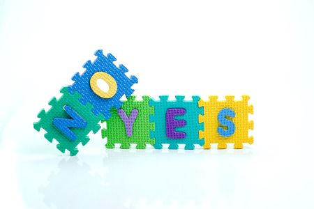 Colorful toy letters on spelling yes no isolated in white background