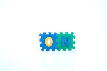 Colorful toy letters on spelling ON isolated in white background
