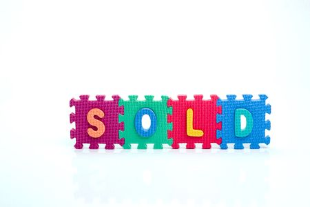 Colorful toy letters on spelling SOLD isolated in white background Stock Photo