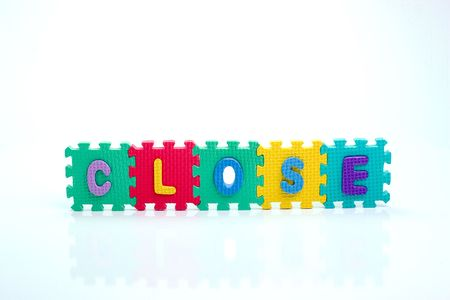 Colorful toy letters on spelling CLOSE isolated in white background