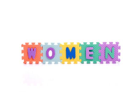 Colorful toy letters on spelling WOMEN isolated in white background