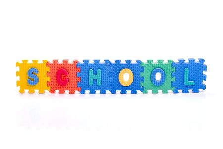 Colorful toy letters on spelling SCHOOL isolated in white background