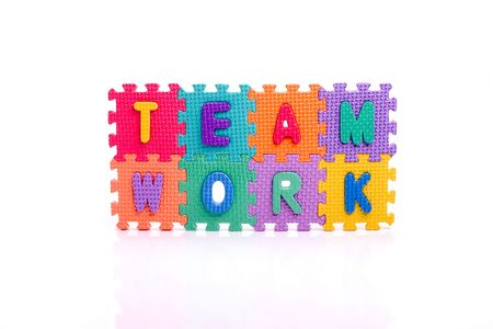 Colorful toy letters on spelling TEAM WORK isolated in white background