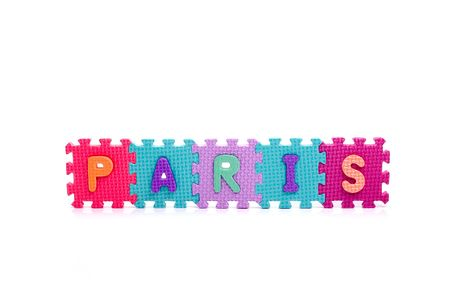 reading material: Colorful toy letters on spelling PARIS isolated in white background