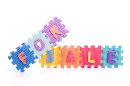 Colorful toy letters on spelling for sale isolated in white background photo