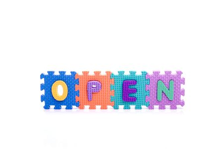 Colorful toy letters on spelling OPEN isolated in white background photo