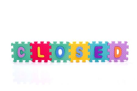reading material: Colorful toy letters on spelling CLOSED isolated in white background