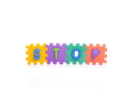 Colorful toy letters on spelling STOP isolated in white background