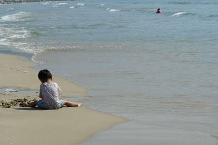 togs: Child playing on beach