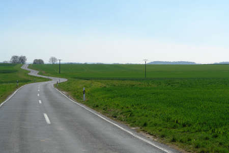 Winding road in rural area with fields and wide open spaces