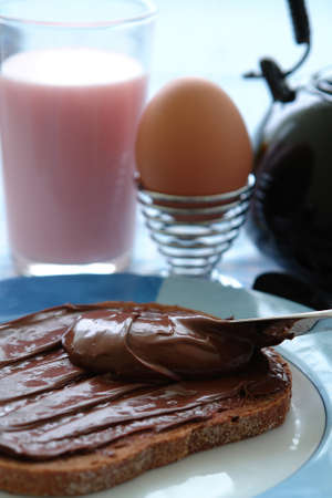 Healthy breakfast for kids with milk, eggs and hazelnut choco on their bread Stock Photo