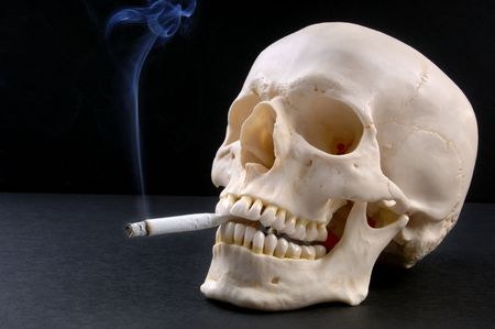 human body substance: A smoking skull (12MP camera).  The skull is anatomically correct (medical model).The lighted cigarette has a smoke trail. Stock Photo