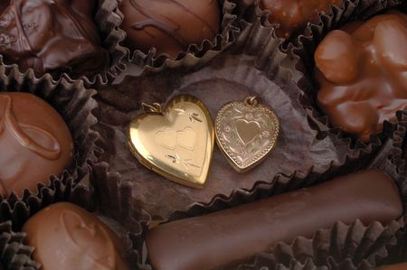 tender sentiment: Two gold hearts among handmade chocolates. Focus = the gold hearts. 12MP camera, macro.