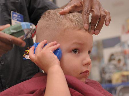conversa: A 3 a�os de edad, muchacho conversaciones sobre un juguete tel�fono celular mientras obtiene un corte de pelo en una barber�a. 12MP c�mara.  Foto de archivo