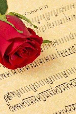 A red rose bud rests on sheet music (parchment paper). Focus is on the rose bud. Stock Photo