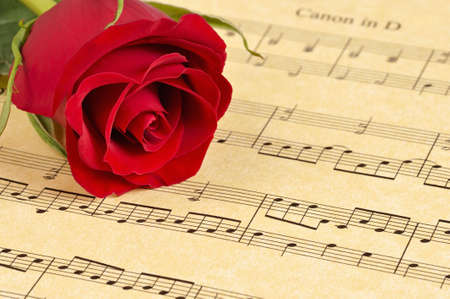 old sheet music: A red rose bud rests