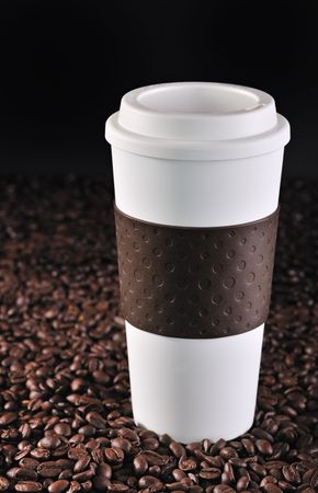 A commuter cup rests on roasted coffee beans.