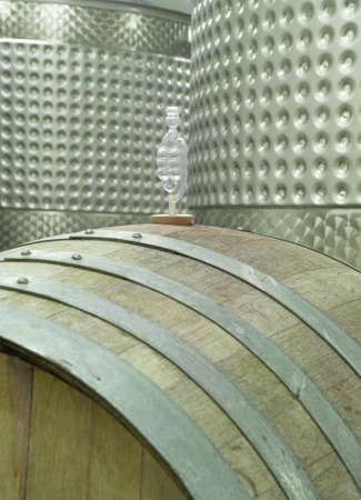 A modern winery cellar in Michigan, USA, shows the traditional (wooden barrel) and modern (steel vats) ways of viticulture.  Atop the barrel is a vent which lets off excess CO2 (carbon dioxide gas).  (14MP camera)