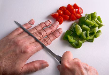 A human hand is being chopped with a knife on a cutting board.