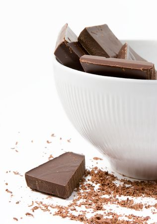 Pieces of dark chocolate in the white bowl with the chocolate shavings lying around Stock Photo