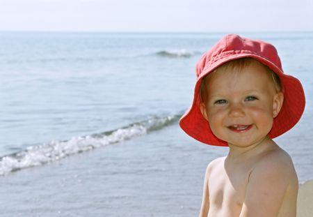 blithe: Feliz sonriente ni�a con sombrero rojo por el mar  Foto de archivo