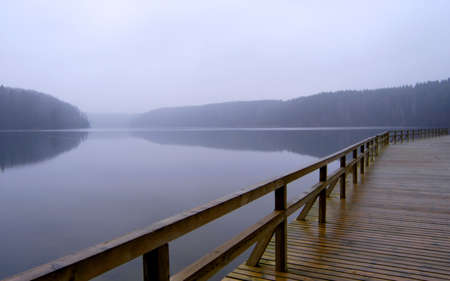 godforsaken: Lonely pier with rail on the foggy lake, tranquil late autumn scenery Stock Photo