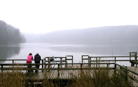 Man and a woman with bicycles enjoy still and tranquil autumn lake view photo
