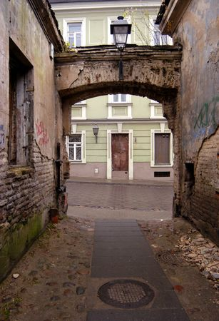 backstreet: Empty desolated backstreet and arch in Vilnius old town, Lithuania Stock Photo