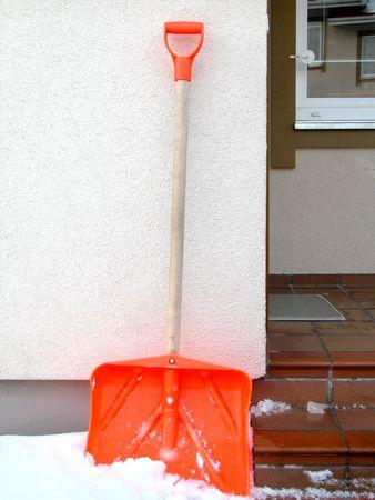 Orange plastic snow shovel against building wall photo