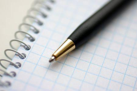 handbook: Spiral checkered white handbook and pen closeup Stock Photo