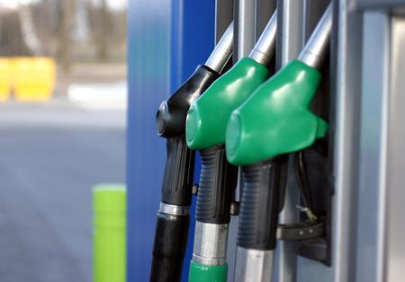 Three gas pump nozzles, two green and one black, closeup  photo