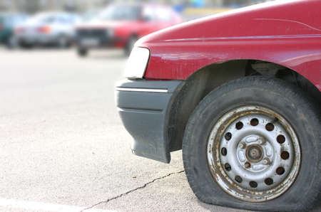 Old useless red car with flat tire